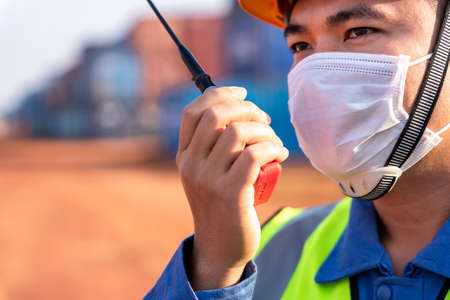 Close up foreman worker wear a mask working use a long distance radio control container cargo harbor to loading containers. Logistics import export shipping concept. 版權商用圖片