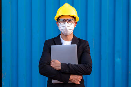 Portrait of Asian Business man import and export goods wear a helmet logitics shipping wear masks protect spreading of Covid 19 by wearing face masks at container background.