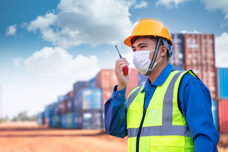 Asian foreman worker wear a mask working use a long distance radio control container cargo harbor to loading containers prevent the spread of the virus. Logistics import export shipping concept.