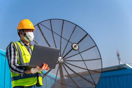 Asian operation and maintenance in satellite dish antennas under sky, engineering team working on checking and maintenance in satellite dish antennas.