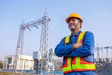 Asain electric engineer confident crossed arms and wear safety  in transmission station, Concept of electric power safety.