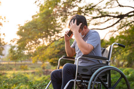 patient or disabled man have anxiety symptoms while talking on the phone sitting and strain on Wheelchair in spring nature, Health treatment concept.