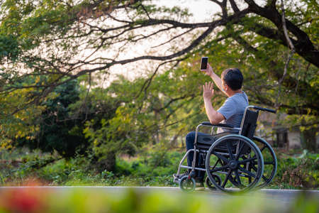 disabled man relax and Online phone in wheelchair at park. 版權商用圖片 - 164141607