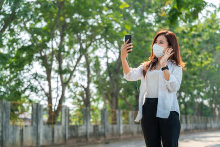 Happy asian woman wears a mask and uses a smartphone to greet her friend, new normal. Archivio Fotografico
