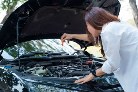 Young asian businesswoman checks the car's engine oil by herself.