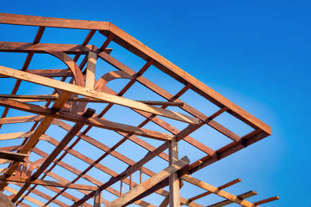 Wooden roof frame of a house against a blue sky. The frame of the cottage. The beginning of the construction of the house, Construction site.