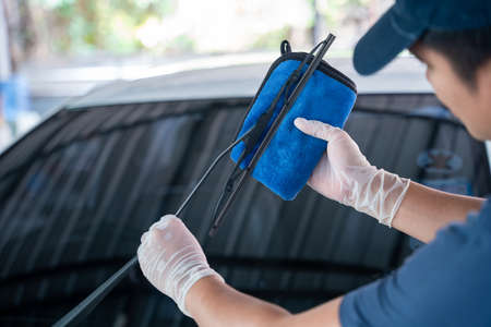 asian man holds the microfiber in hand and wipe the windshield wipers the car, Car wash service concept.