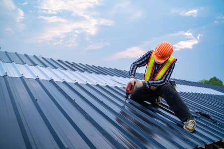 Asian Roofer worker safety wear using air or pneumatic nail gun and installing on new roof metal sheet, Roof concept of residential building under construction.