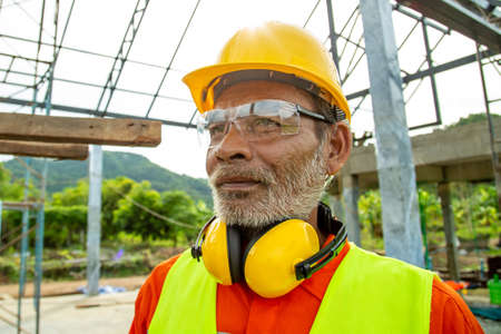 Portrait of Engineer technician senior worker in analyzing an Unfinished Construction Project.