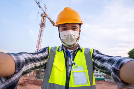 Portrait Selfie of Engineer wearing PPE and face mask protect  virus  working at construction site