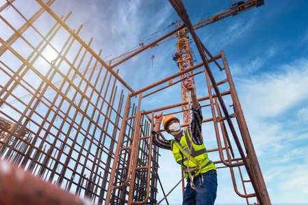 Asian worker working on steel structure at height equipment constructive at construction site. Fall arrestor device for worker with hooks for safety body harness.