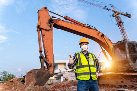 Haapy foreman construction excavator, engineer or worker backhoe driver and crane wearing a safety suit  at construction site