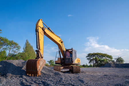 Crawler excavator parked on stone ground on blue sky background at construction site