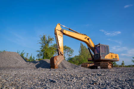 Crawler excavator digging in construction site on demolition site on blue sky background