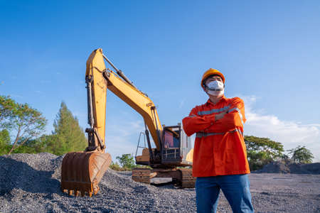 Driver crawler excavator digging in construction site on demolition site on blue sky background 版權商用圖片