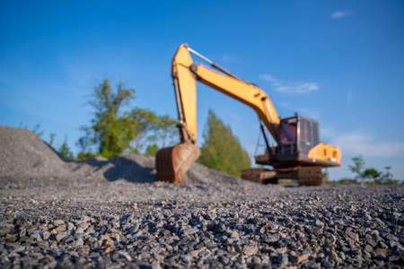 Selective focus stone in the foreground and Blurred of Crawler excavator digging in construction site on demolition site on blue sky background 版權商用圖片