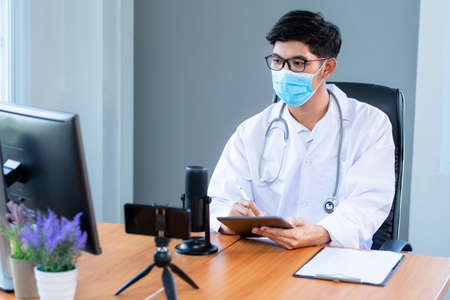 New normal, medical team wearing medical masks technology network team meeting concept. Doctor at a table discussing a patients records working, Online medical 版權商用圖片