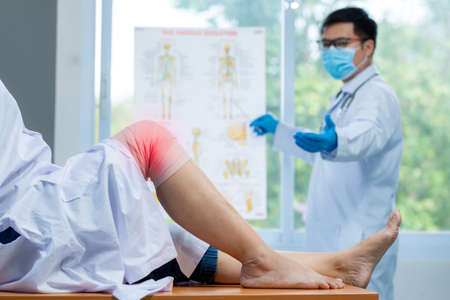 Selective focus knee, Orthopedic doctor wear medical gloves doctor examining head of patient with knee problems inflammation in clinic.