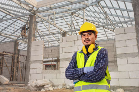 Portrait of construction engineer technician worker, Civil engineer checking work roof structure of unfinished house at the construction site, House construction concept.