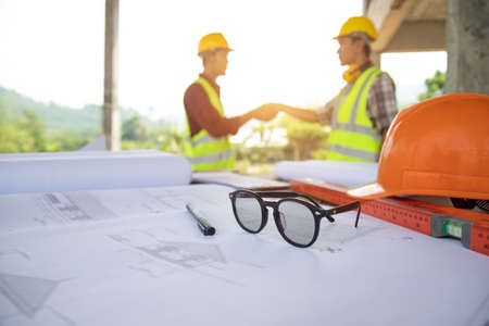 Select focus glasses of Team work construction engineer and architects working handshake after meeting discussing designing planing measuring layout of building blueprints in construction site