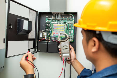 Electrician working use digital clamp meter in hands of electrician, close-up against background of electrical wires and relays. Adjustment of scheme of automation and control of electrical equipment 版權商用圖片
