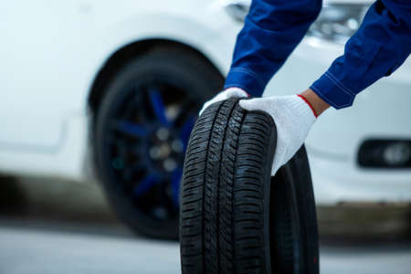 Close up of car mechanic's hand holds a tire, New tires that change tires in the auto repair service center, new car tires and blurred background
