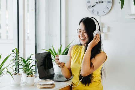 Portrait of happy asian woman listen to music with headphones in coffee shop, cafe 版權商用圖片