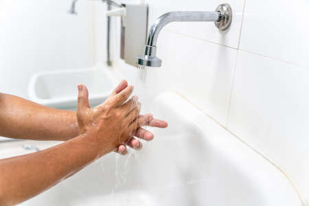 hand of man wash your hands at the wash basin with foam, cleanse the skin and have water flowing through the hands. Health for COVID-19 prevention concepts