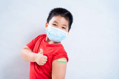 Happy asian boy or child wearing a mask in the shoulder with plaster on arm after vaccination on a white background, Concept of vaccination against the coronavirus or COVID-19