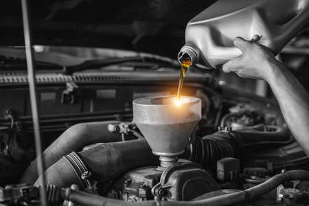 Close up hand of an auto mechanic changes the oil, Refueling and pouring oil quality into the engine motor car Transmission and Maintenance Gear. Energy fuel concept.