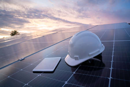 helmet with tablet on the solar panel for working solar station photovoltaic panels, Science solar energy,engineer working on checking and maintenance equipment at industry solar power