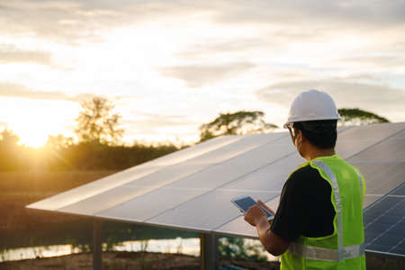 The solar farm or solar panel with Solar cell engineer using a tablet check and maintenance equipment at industry solar power, Photovoltaic module idea for clean energy production.