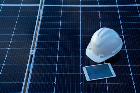 Top view of helmet with tablet on the solar panel for working solar station photovoltaic panels, Science solar energy,engineer working on checking and maintenance equipment at industry solar power