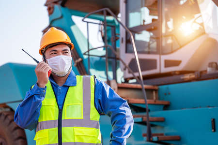 Portrait of warehouse asian man worker driver truck driver crane lifting up container with safety equipment standing in front of big forklift use radio to communicate with trucks at container yard.