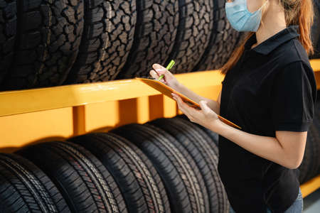 close up female worker wear a mask to prevent the spread of corona virus or COVID-19 checking the stock of car tires at warehouse and writing some notes. Stock Photo