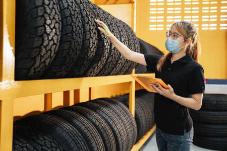 Asian female worker wear a mask to prevent the spread of corona virus or COVID-19 checking the stock of car tires at warehouse and writing some notes.