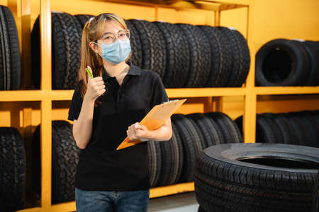 Happy asian female worker wear a mask to prevent the spread of corona virus or COVID-19 checking the stock of car tires at warehouse