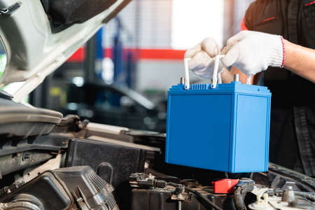 Close up hand of Male mechanic changing car battery, engineer is replacing car battery because car battery is depleted at car service center.