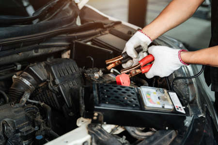 Close up hand of Car repairman with multimeter device for check up car battery life, battery inspection
