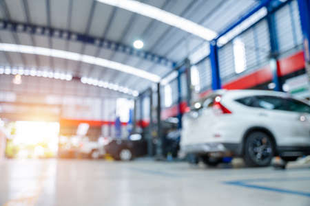 blurred of car repair station paved with epoxy floor and electric lift for a car that comes to change the engine oil in the background of maintenance car service center. Stock Photo