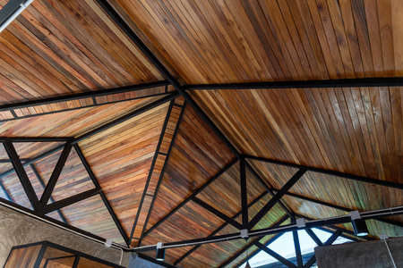 The structure under the roof is decorated with wood at building site of a house