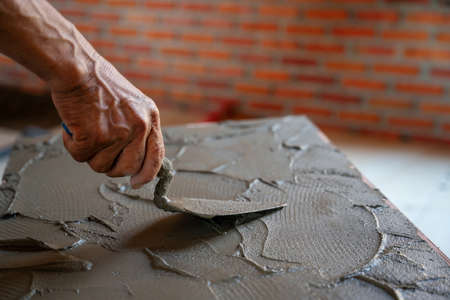 closeup hand of tilers use trowel adhesive mortar for floor tiles for building house