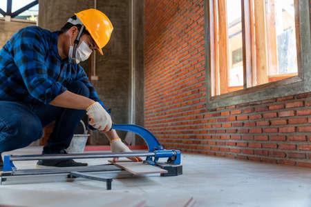 artisan tiler, Industrial tiler builder worker working with floor tile cutting equipment at construction site