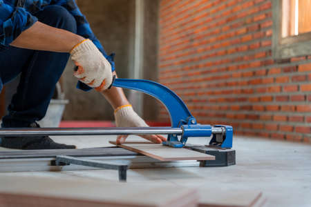 Close up hand of an artisan tiler at construction site, worker cuts a large slab of tile during the construction of a house.
