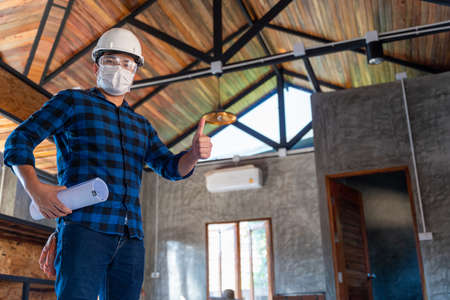 Happy asian construction engineer technician inspect the wood structure under the roof at construction site or building site of a house. Stock Photo