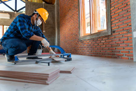 Asian artisan tiler at construction site, worker cuts a large slab of tile during the construction of a house, floor tile cutting equipment