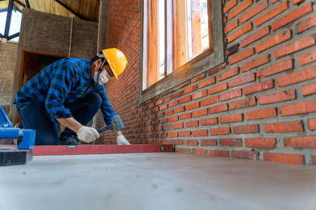 artisan tiler hands working on a new house entrance, local and professional handyman applying tiles at construction site Stock Photo