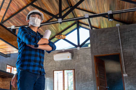Happy asian construction engineer technician standing with arms crossed confidently after inspect the wood structure under the roof at construction site or building site of a house. Stock Photo