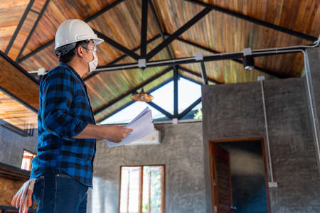 Construction engineer technician inspect the structure under the roof at construction site or building site of a house.