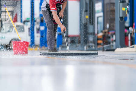 service staff man using a mop to remove water in the uniform cleaning the protective clothing of the new epoxy floor in an empty warehouse or car service center. Stock Photo